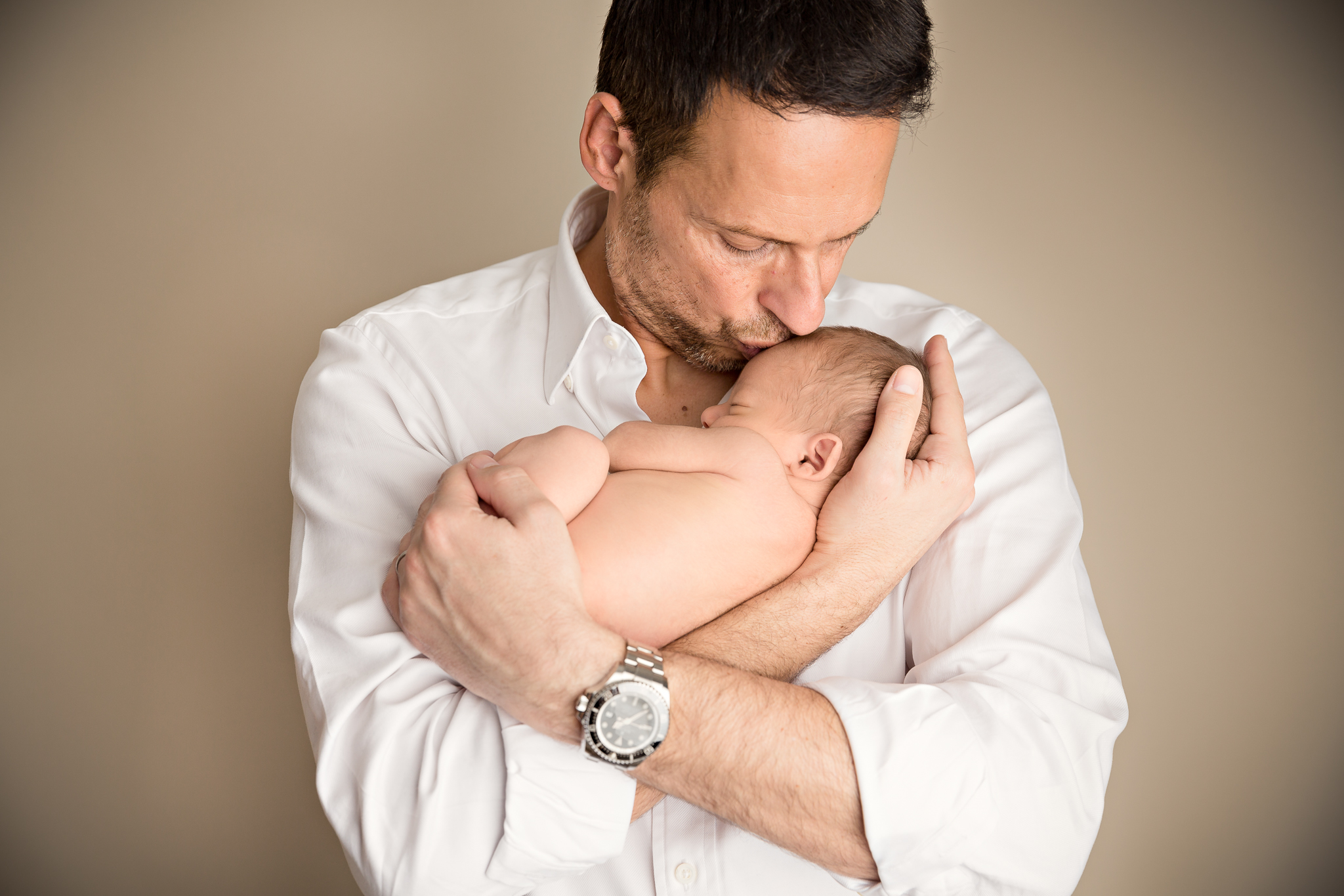 sleeping baby being haeld by his father during a newborn baby photography session in hampshire