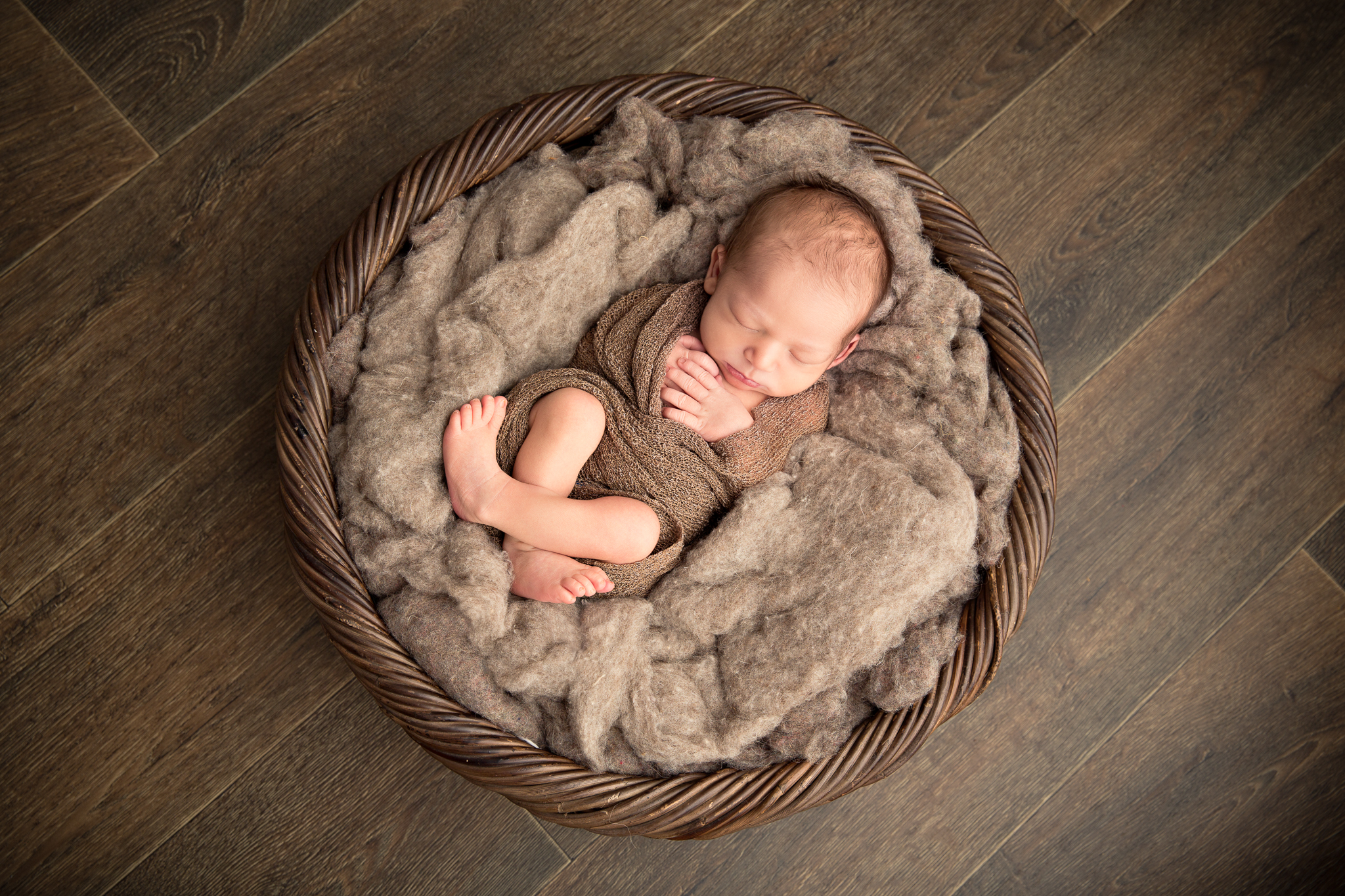 baby boy captured sleeping in a wooden basket during a newborn baby photography session in berkshire