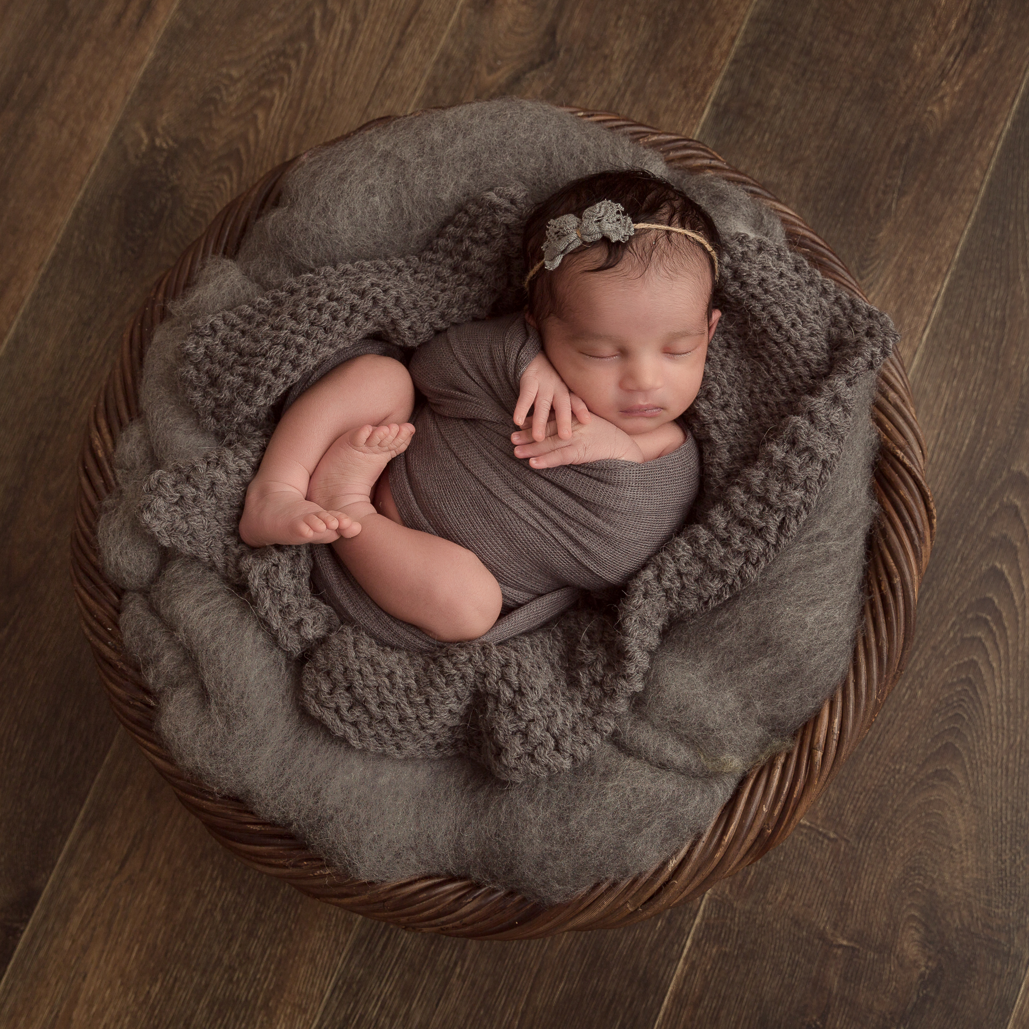 baby girl in a wooden basket captured during a newborn baby photography session in berkshire
