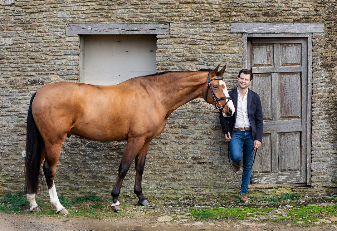 man-standing-infront-of-a-cotswold-barn-with-a-horse-during-a-professional-photoshoot