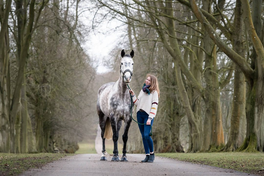 lady-standing-wither-her-horse-in-a-tree-lined-drive-during-a-winter-equine-photoshoot