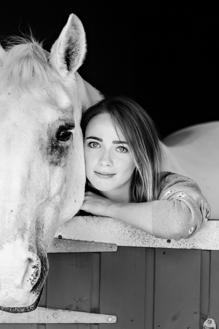 simple-black-and-white-cropped-portrait-of-a-lady-and-horse-leaning-over-a-stable-door