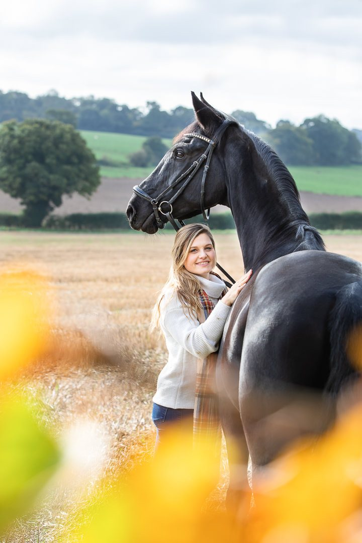 lady-and-her-horse-in-a-field-with-autumn-foliage-in-the-foreground