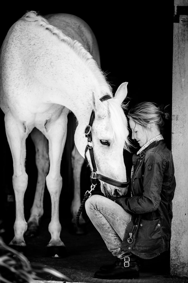 simple-black-and-white-portrait-of-a-lady-and-her-horse-in-a-stable-doorway