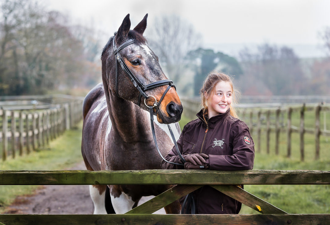 girl-and-her-horse-leaning-on-a-gate-during-a-professional-equine-photoshoot