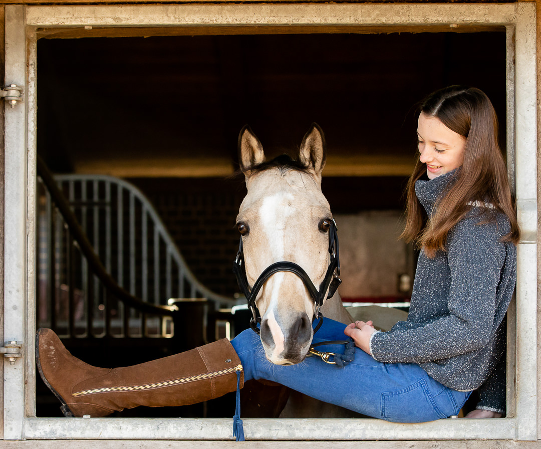 girl-sitting-in-a-stable-window-with-her-horse-looking-out