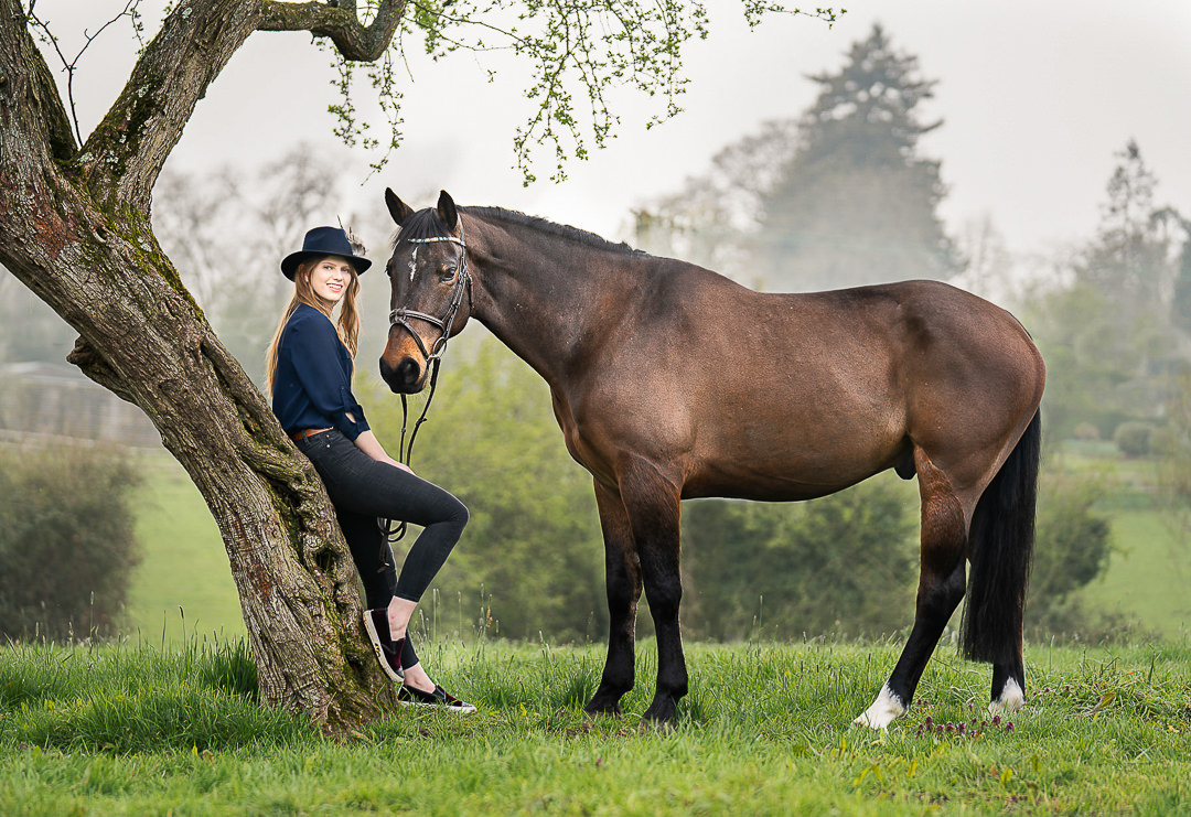 girl-leaning-against-a-tree-with-a-cool-hat-and-standing-with-her-horse
