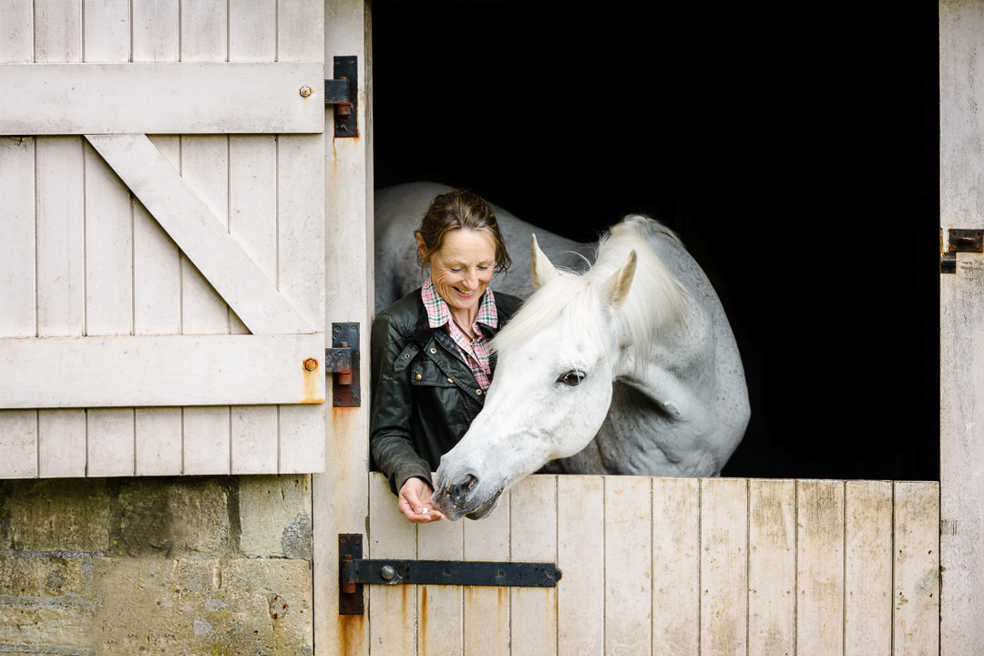 lady-smiling-with-her-horse-looking-out-of-a-stable-door-and-reaching-for-a-treat