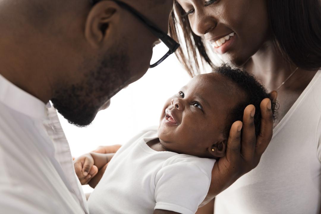 baby-girl-held-between-mum-and-dad-smiling