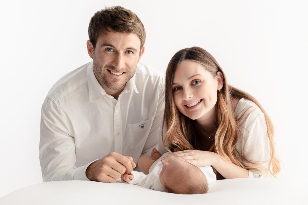mum-and-dad-and-newborn-baby-in-a-white-studio