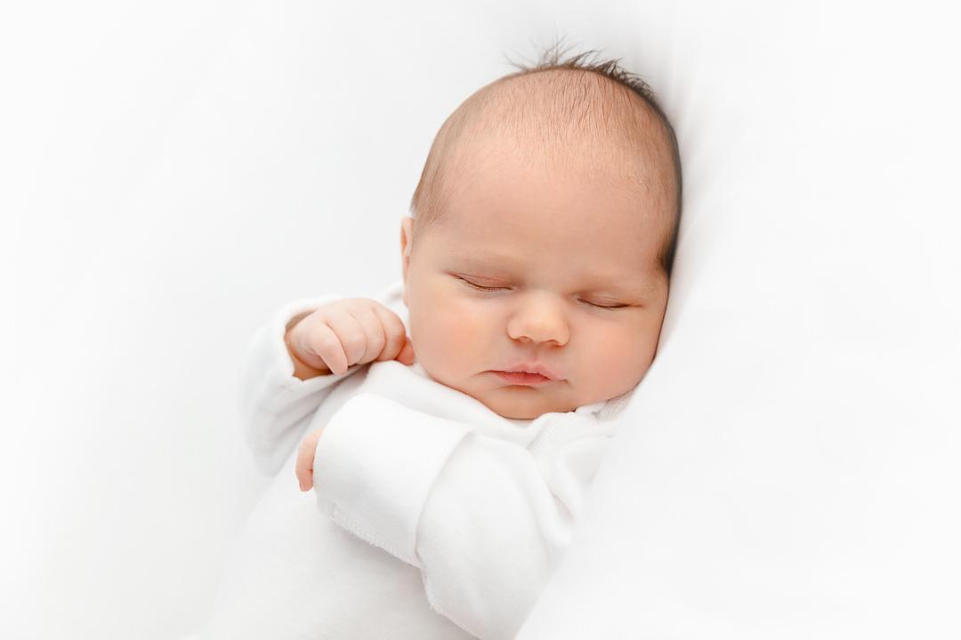 Newborn-baby-in-a-white-studio-taking-part-in-a-newborn-photoshoot