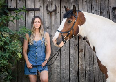 lady-and-coloured-horse-posing-in-front-of-a-rustic-farm-building