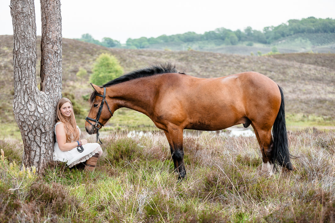 girl sitting against a tree with her horse in the new forest hampshire
