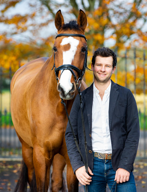 man in a smart jacket posing with his horse during an equine photoshoot