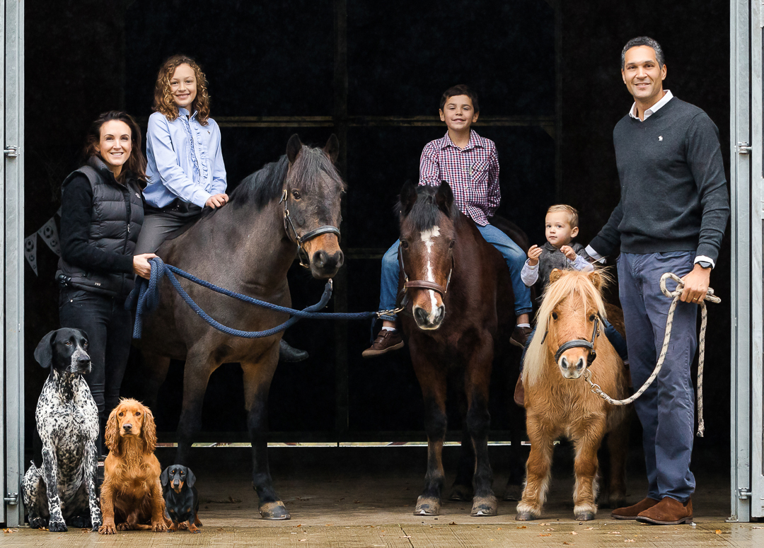 Whole family photograph with parents, children, horses and dogs