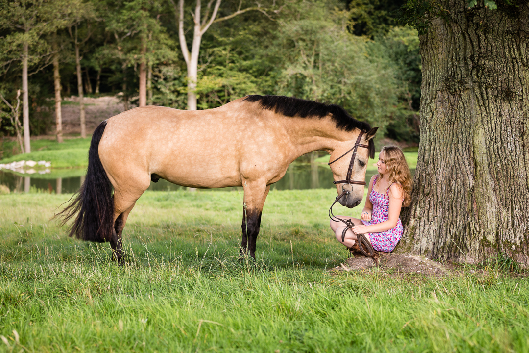 girl sitting under a very old oak tree with her horse