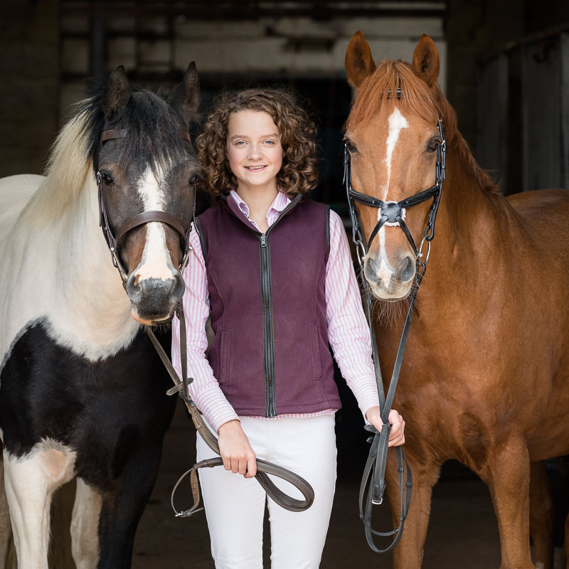 teenage girl standing with her two ponies in a barn entrance during an equine photoshoot