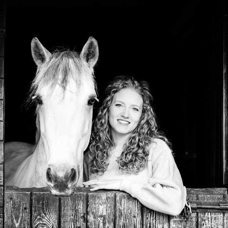 lady standing behind a stable door with her horse during an equine photoshoot
