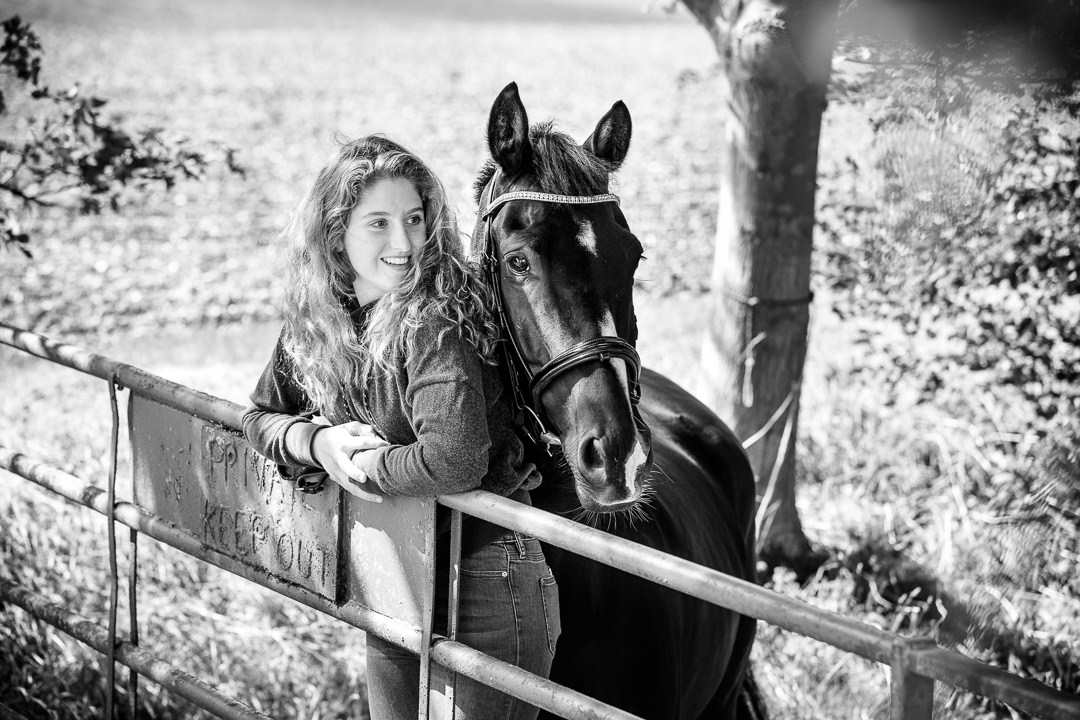 black and white photography of a girl resting on a fence with her black horse