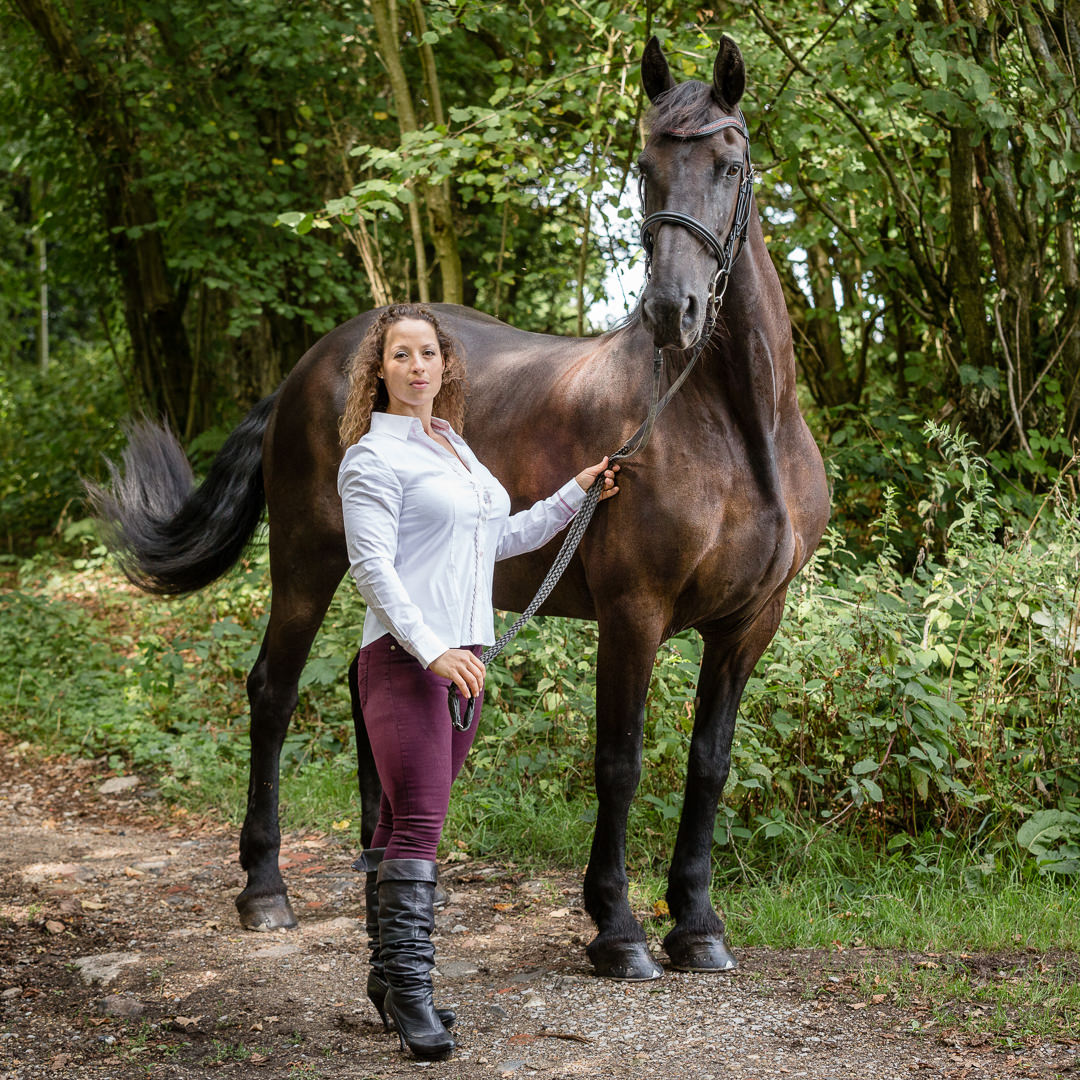 lady standing with her friesian horse during a photoshoot in hunfgerford