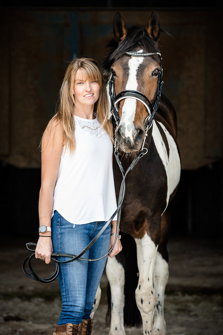 lady standing with her coloured horse in a barn doorwat during an equine photoshoot