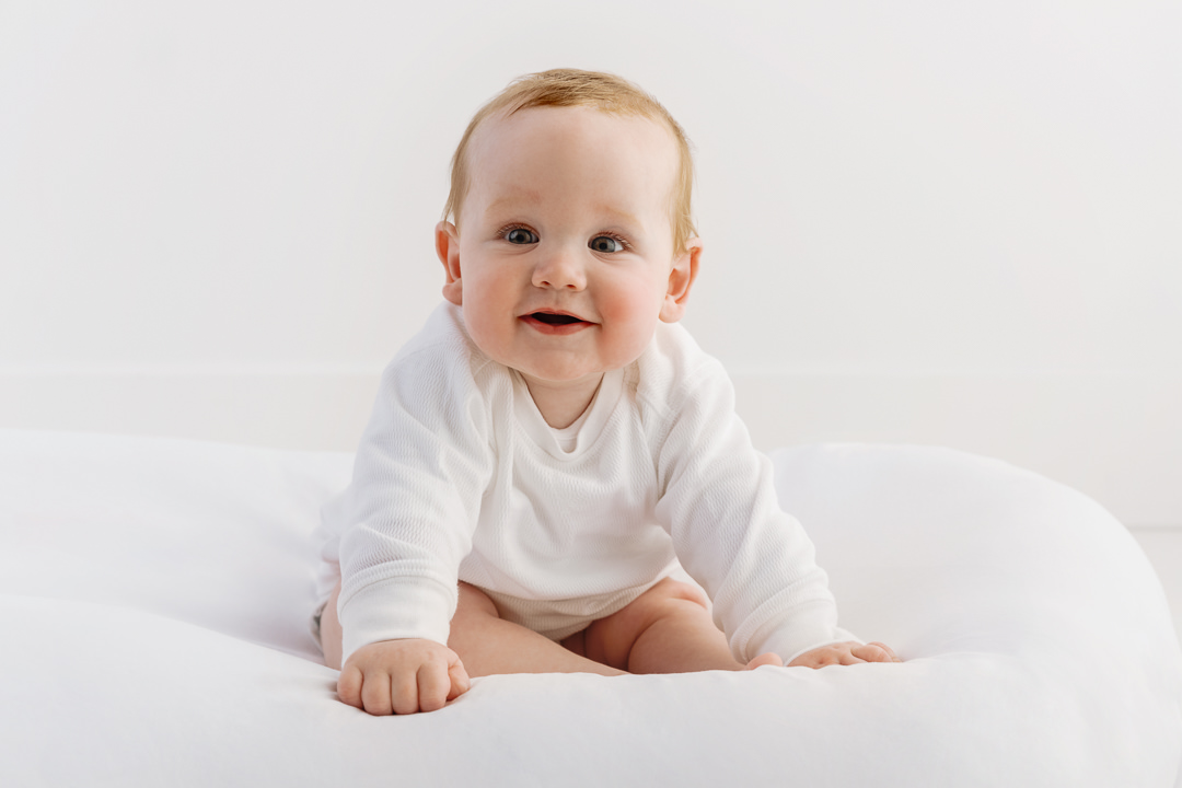 smiling baby boy sitting up in a pure white baby phontography studio