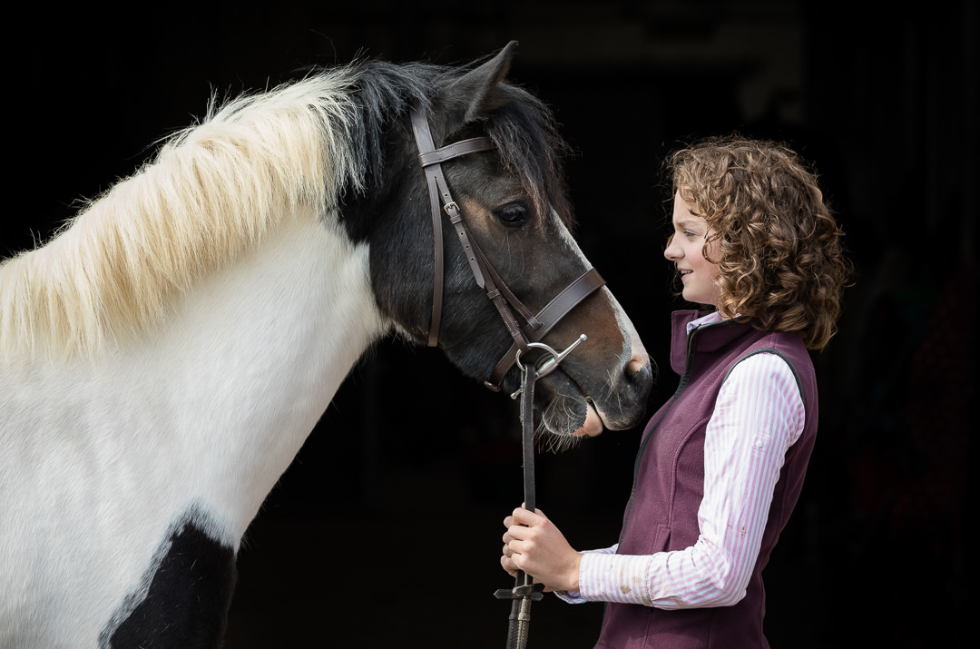 girl looking in to her pony's face during an equine photoshoot