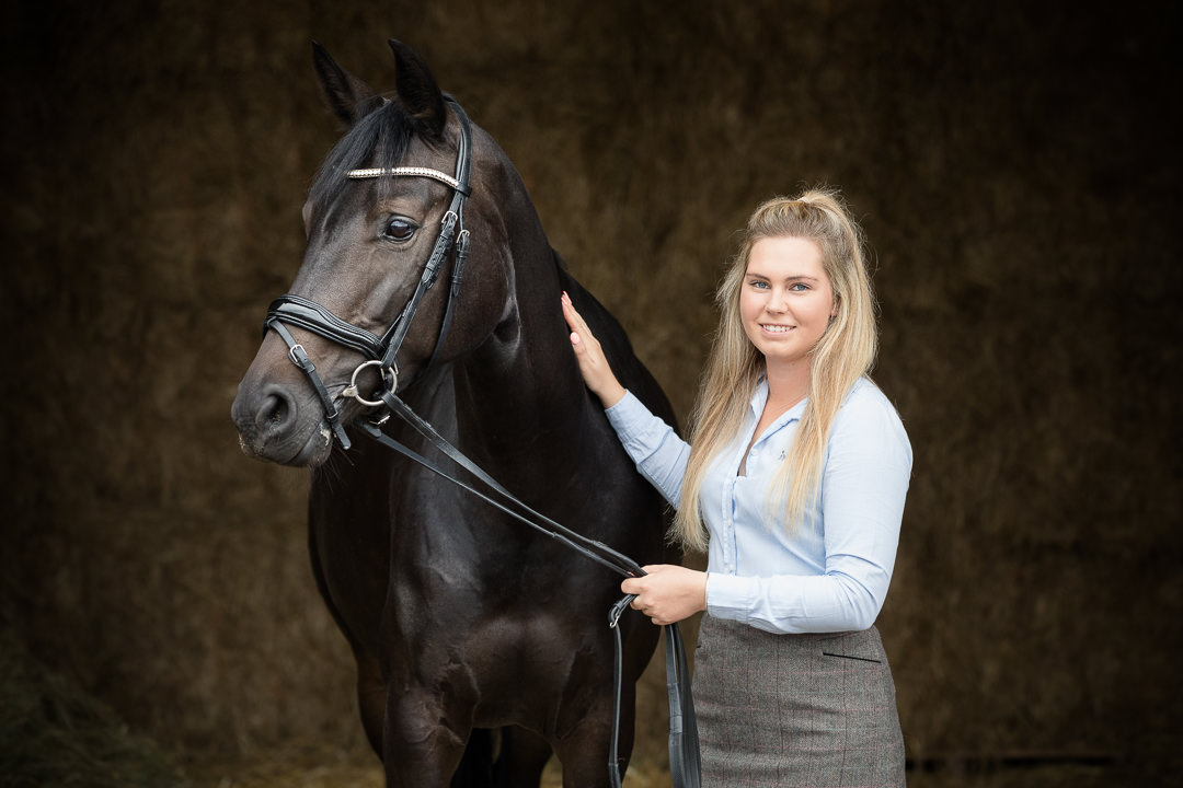 lady standing with a dressage horse in a straw barn