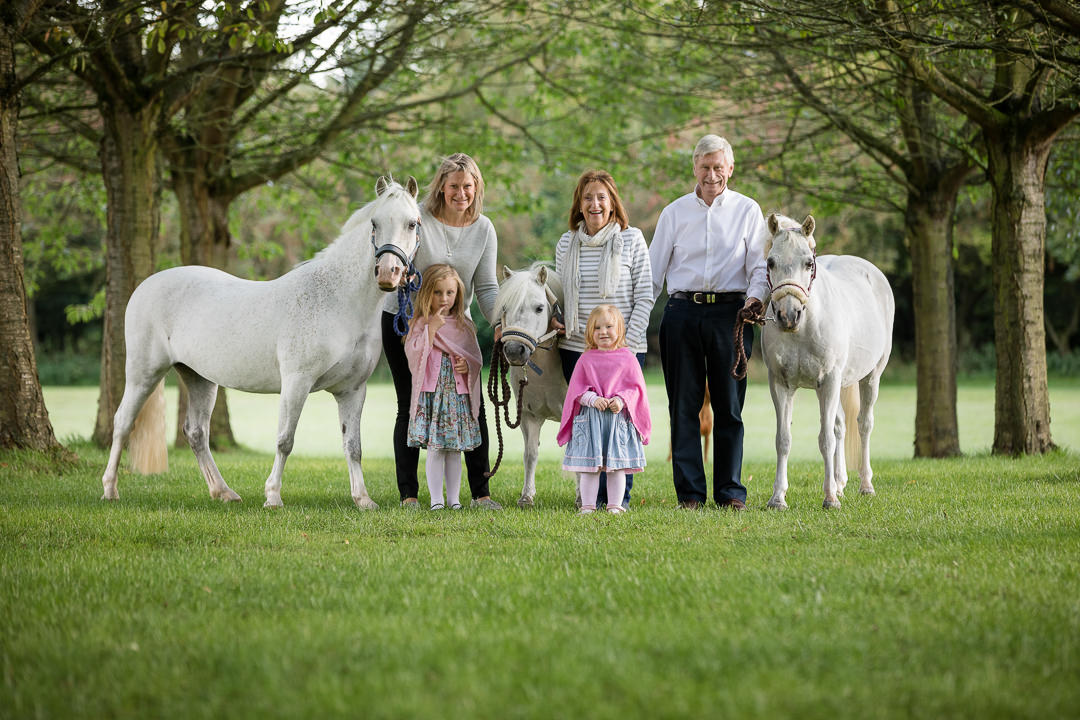 grandparents mum and two little girls with three white ponies all standing in a field