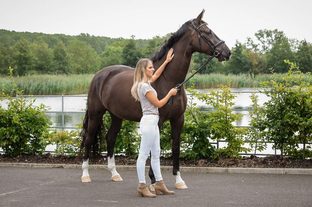 lady standing in front of a lake with dressage horse