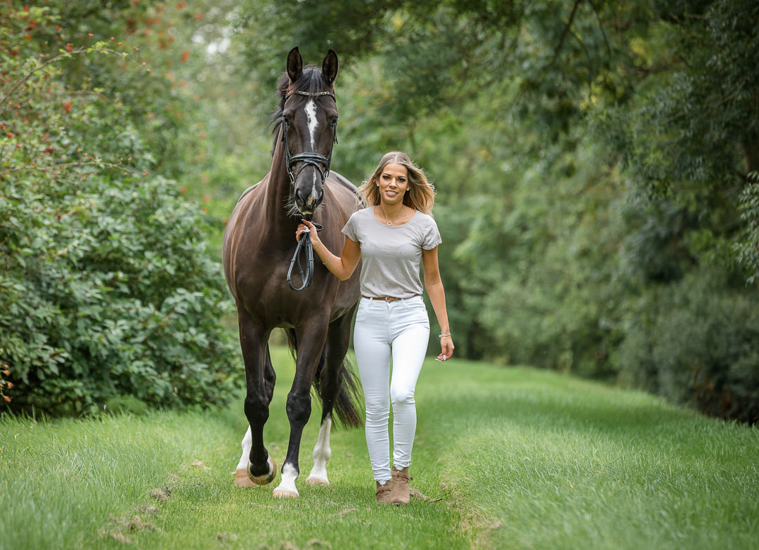 lady walking with a very beautiful dressage horse down a tree lined avenue