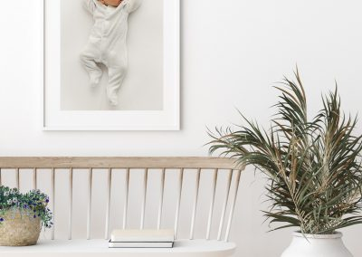 simple_cute_baby_photography_image_of_a_baby_in_a_white_baby_grow_framed_and_hung_on_the_wall