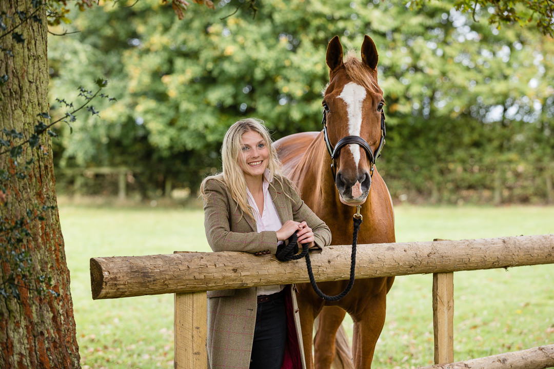 lady looking over a field fence with her horse during an autumn photoshoot in buckinghamshire