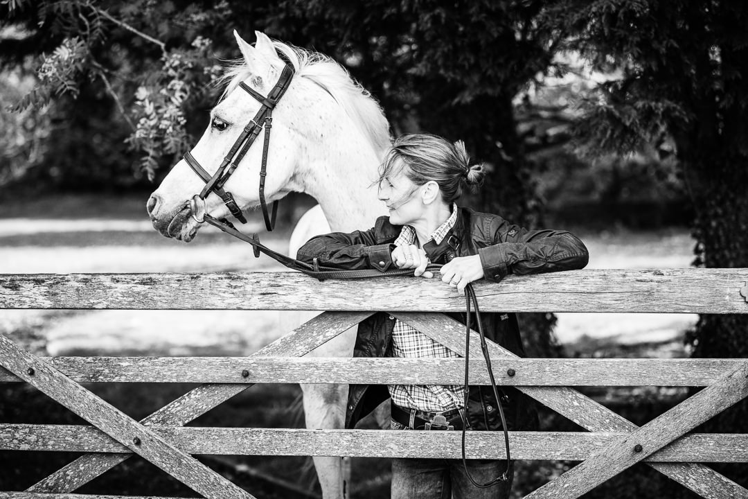 black and white photograph of a lady with her horse leaning over a 5 bar gate