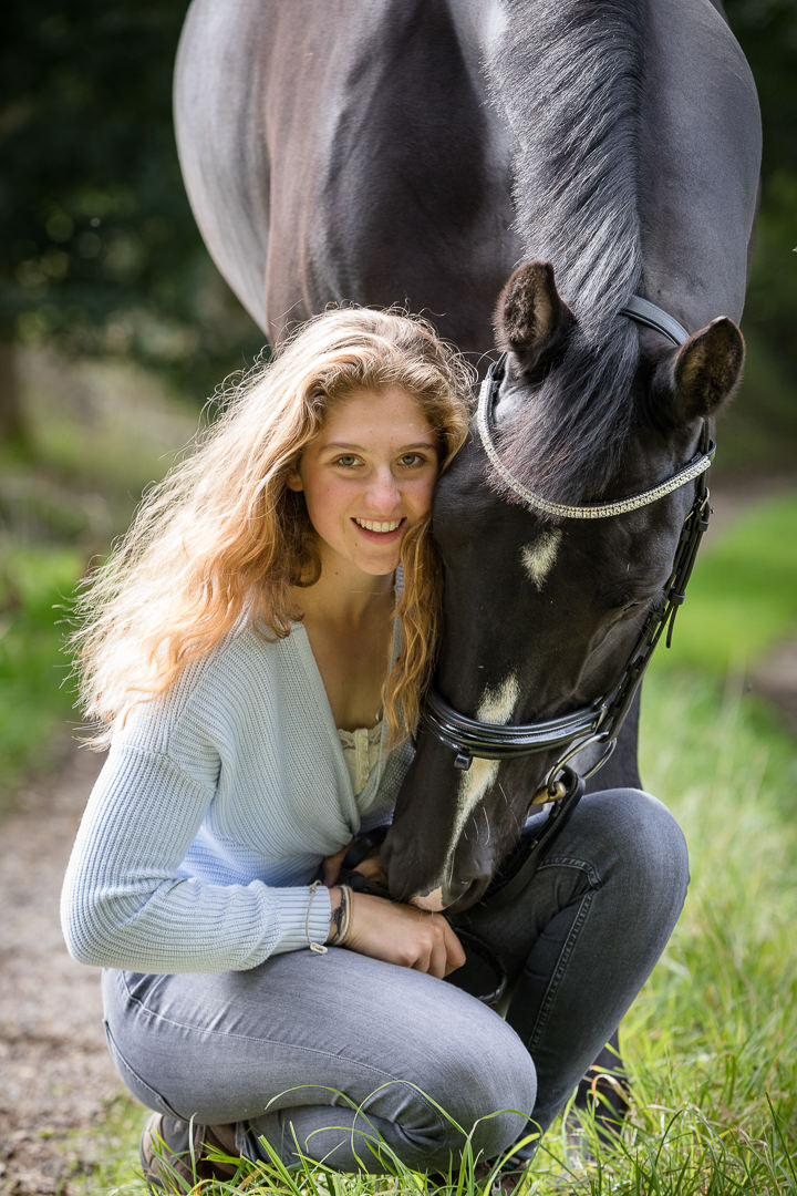 girl kneeling with her horse in a casual pose