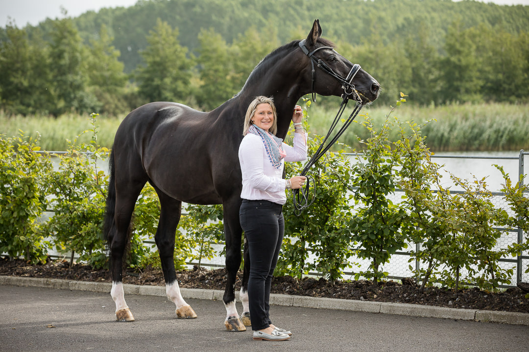lady standing by a lake with her black stallion
