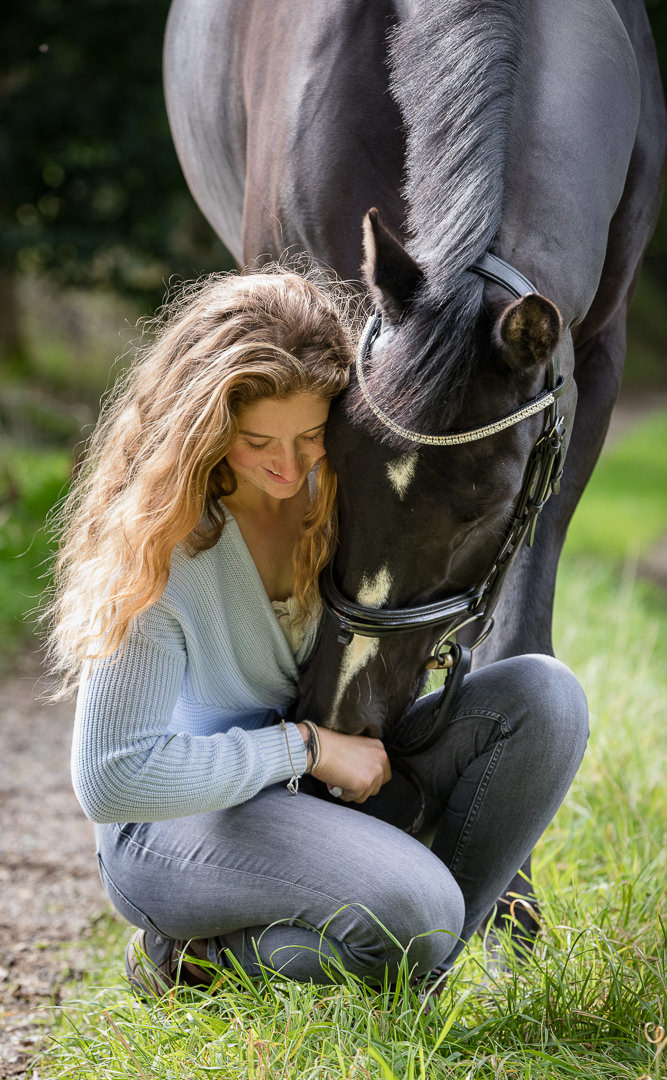 girl kneeling whilst her horse comes in for a nuzzle