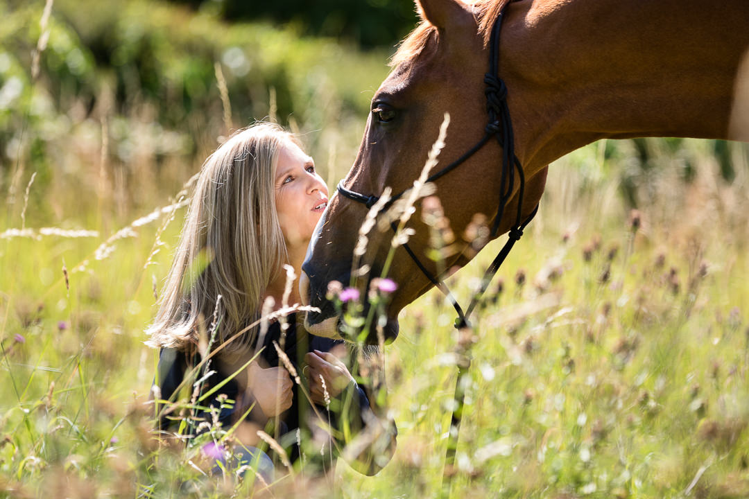 lady in a summer meadow gazing up at her horse during an equine photoshoot