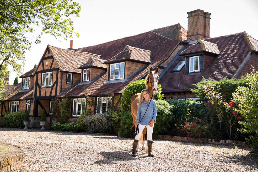 lady standing in front of her house with her chestnut dressage horse