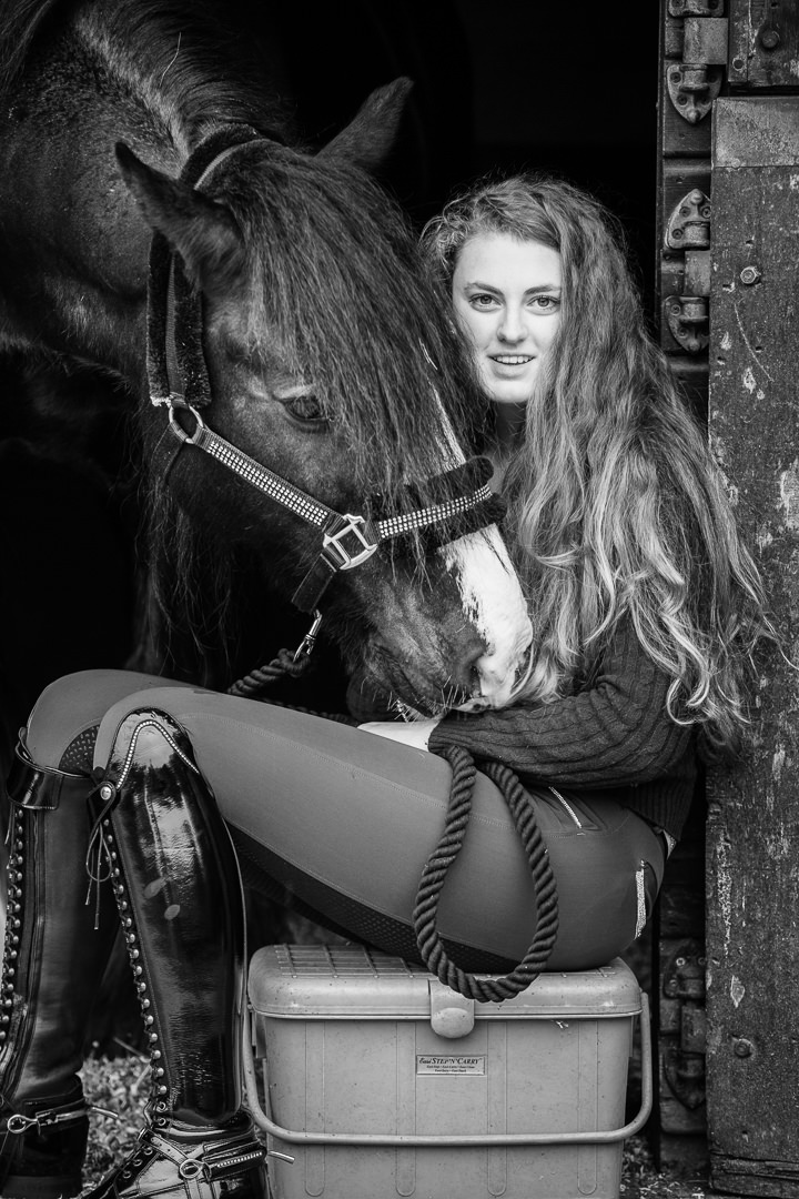black and white image of a girl sitting in a stable doorway with her dressage cob