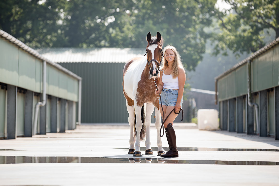 girl posing with her horse on a hot summer's day with shorts and a vest top