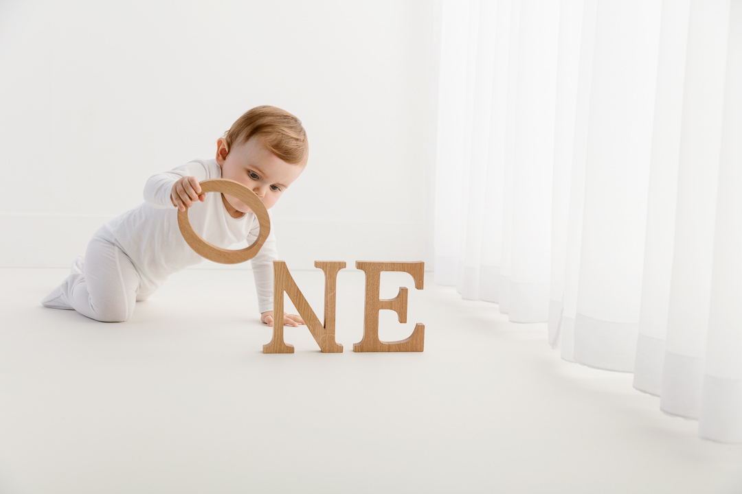 little boy picking up a wooden letter during a cake smash baby photoshoot