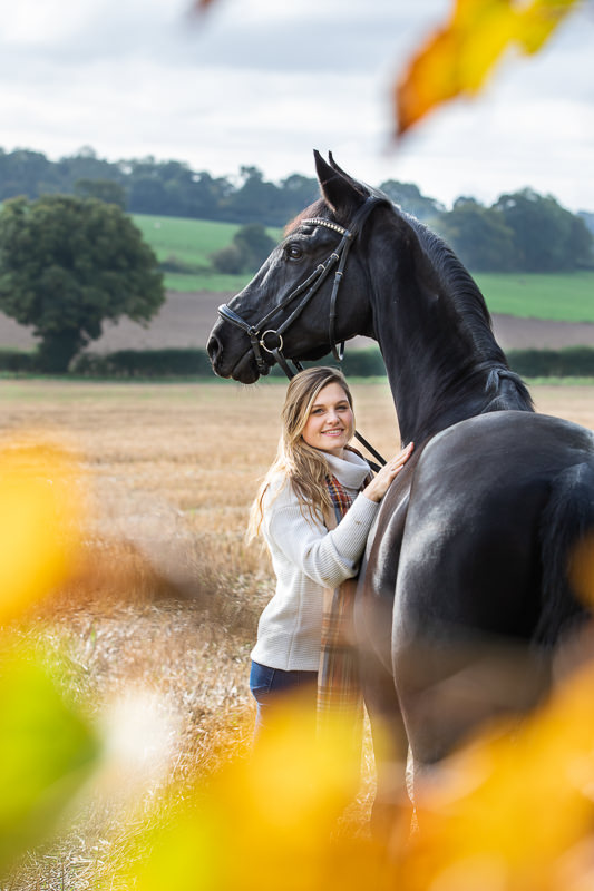 lady standing with her horse in an usutmn setting