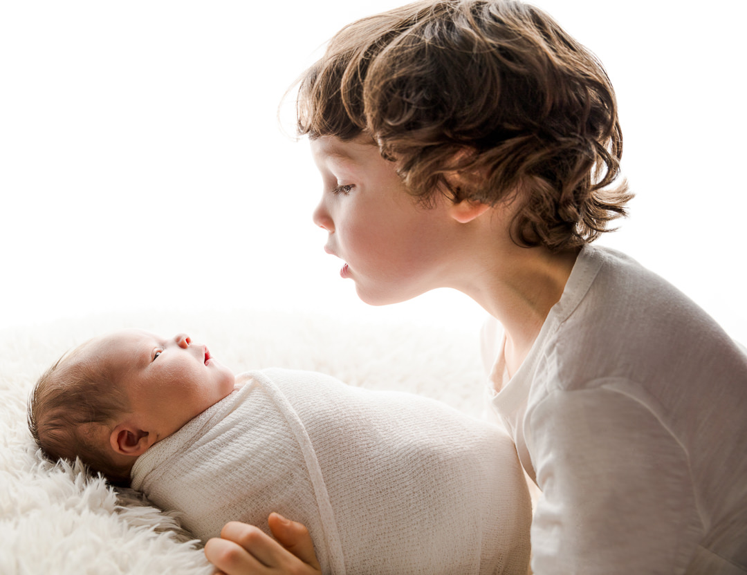 little boy looking at his newborn baby girl during a newborn photoshoot
