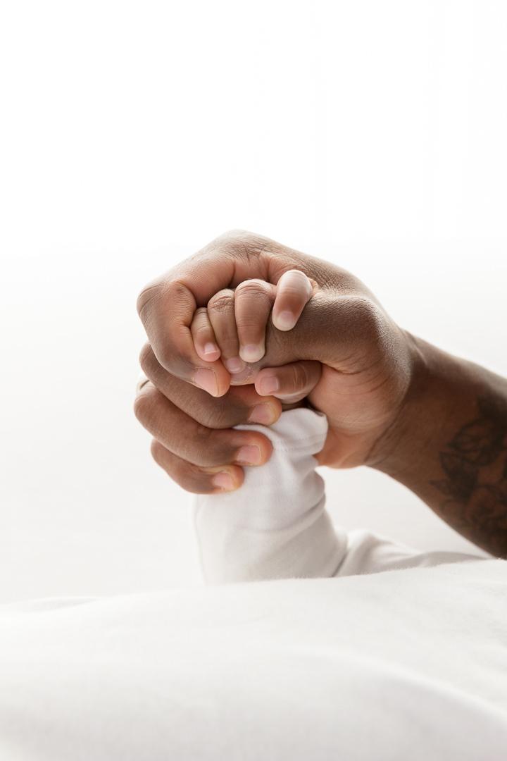 tiny newborn baby hand being held by her Mum's hand