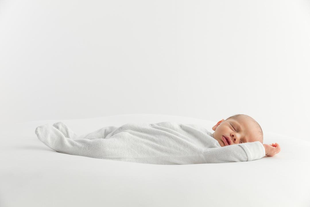 sweet little newborn baby lying on it's back during a newborn photoshoot