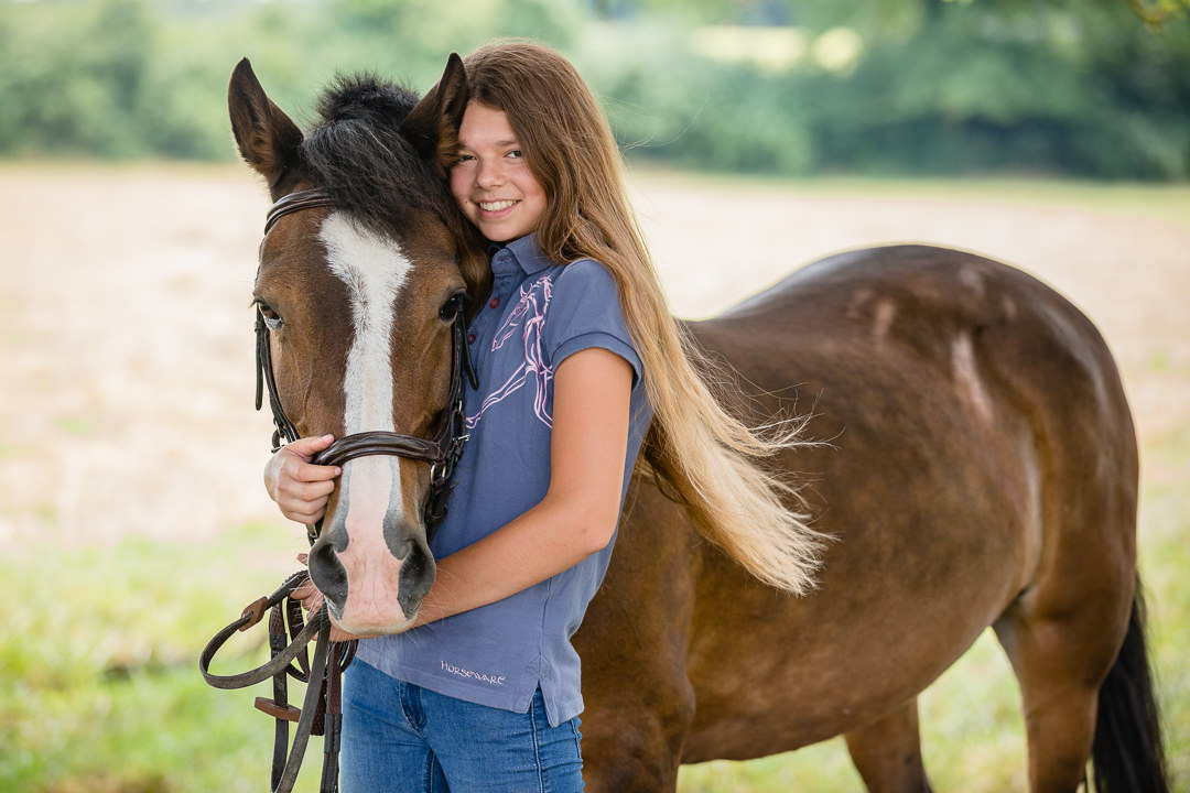 girl cuddling her pony in a summer meadow