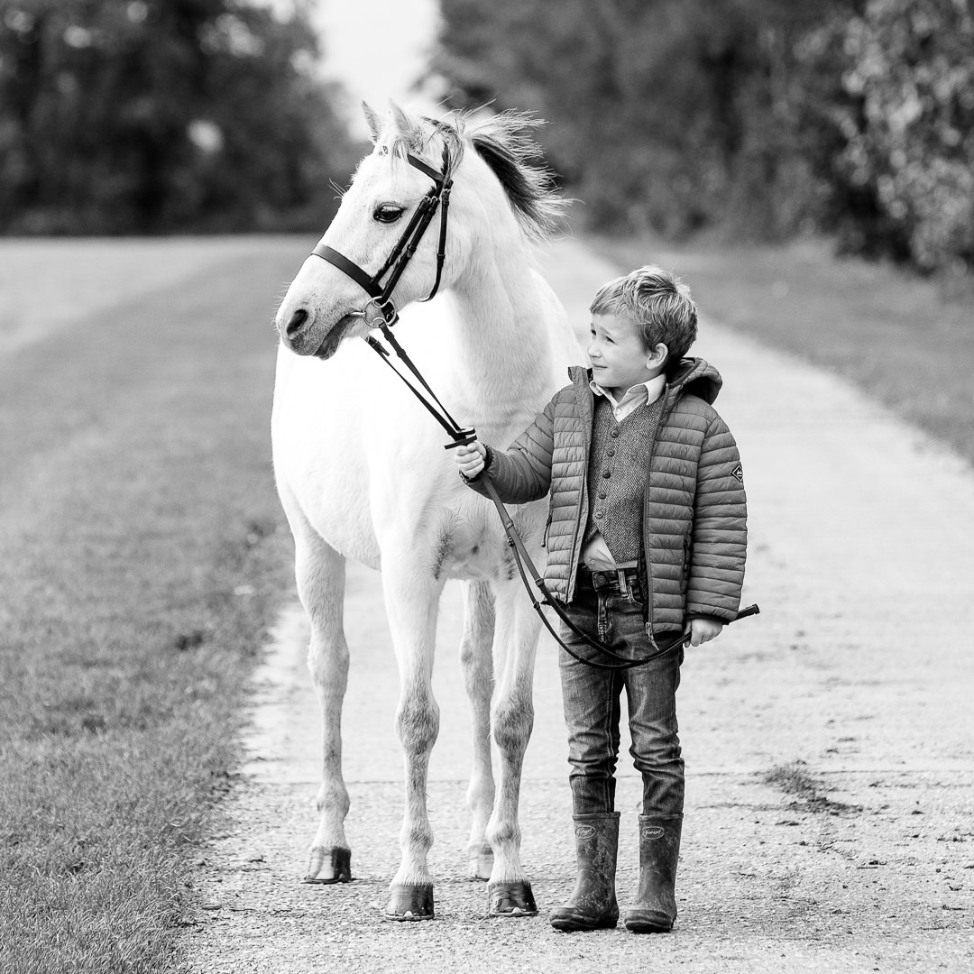 black and white winter photoshoot of a little boy with his white pony