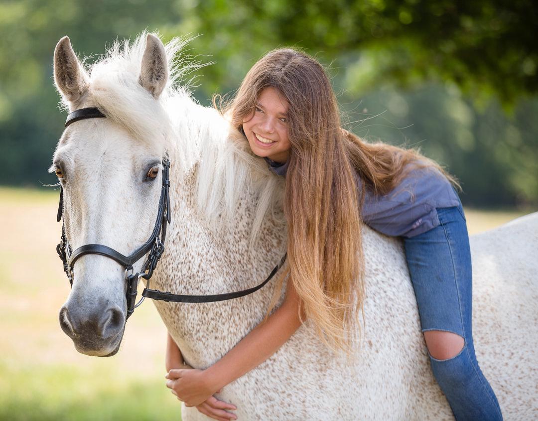 girl sitting bareback on her pony hugging it's neck
