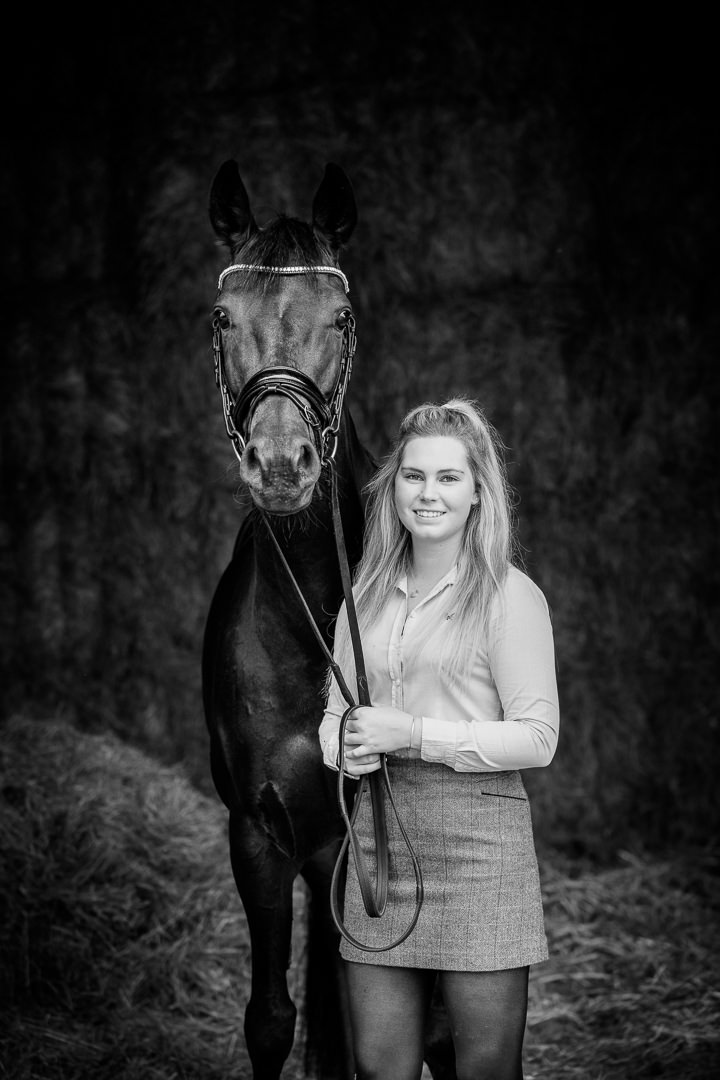 black and white equine portrait of a girl standing in a barn entrance with her black horse